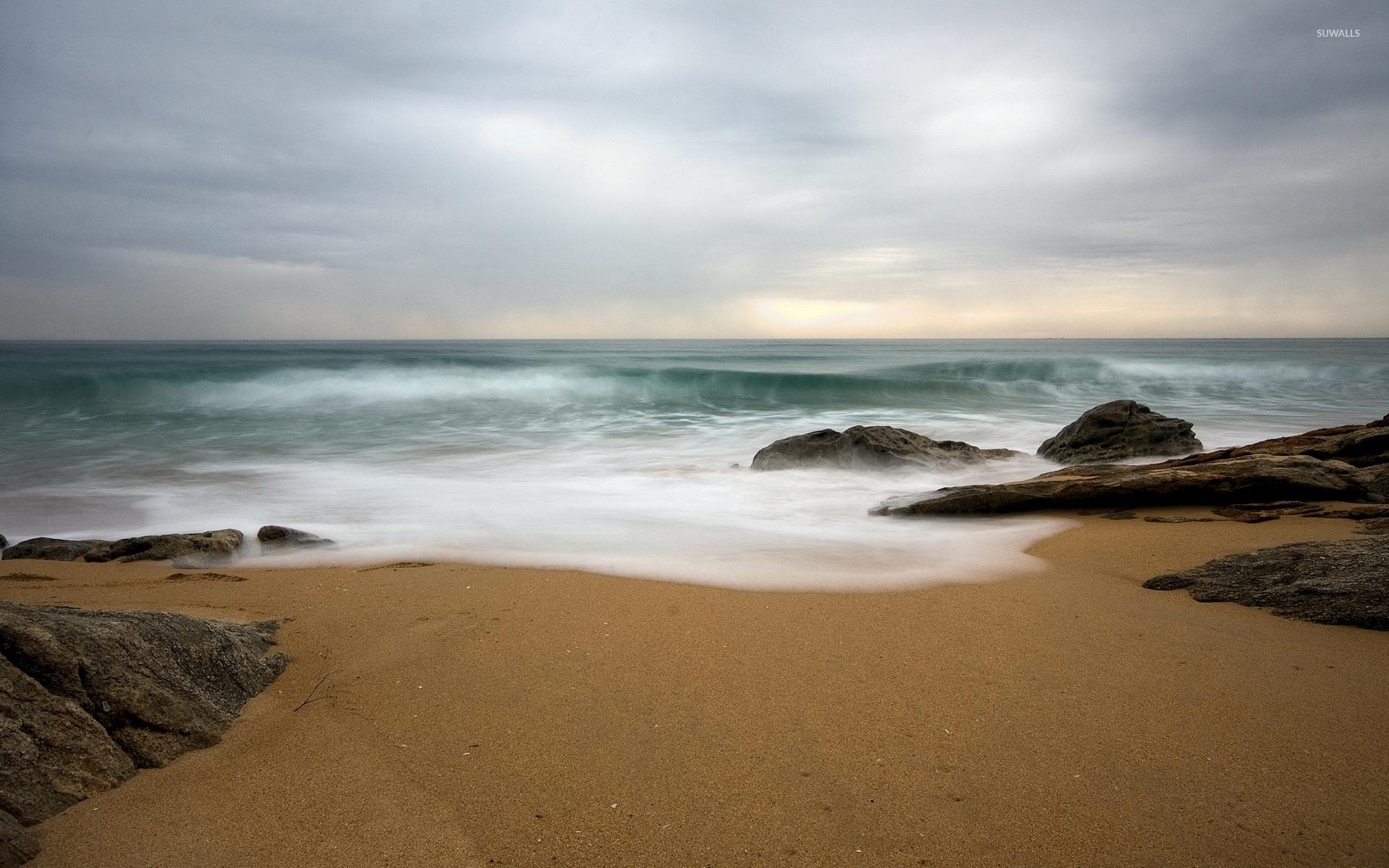 Sandy Beach Wallpaper: Waves Resting On The Sandy Beach Wallpaper