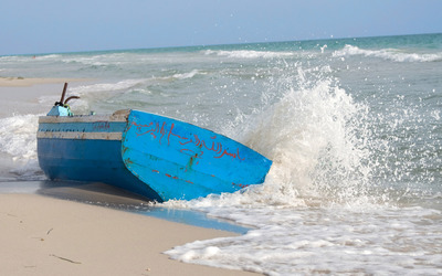 Waves splashing on a blue boat on the beach wallpaper