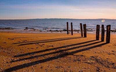 Wood pillars on the sandy beach wallpaper