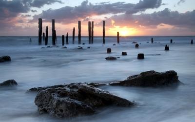 Wooden pillars standing tall towards the ocean sunset wallpaper