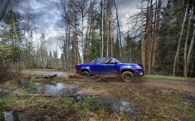 Blue Chevrolet Colorado Z71 racing through muddy forest path wallpaper