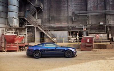 Blue Ford Mustang RTR parked in front of a factory wallpaper