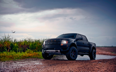Front side view of a black Ford F-150 Raptor wallpaper