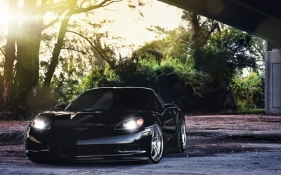 Front view of a black Chevrolet Corvette with headlights on wallpaper