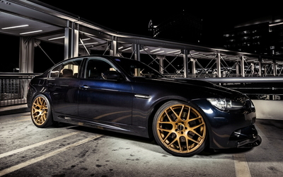Golden rims on a BMW M3 with wallpaper