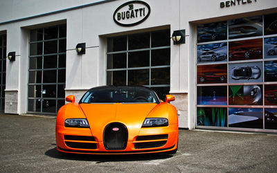 Orange Bugatti Veyron parked in front of a showroom wallpaper