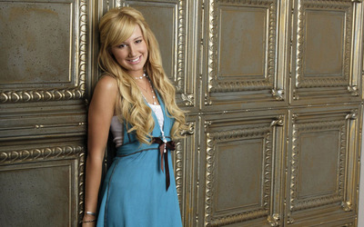 Ashley Tisdale leaning on a wall wallpaper