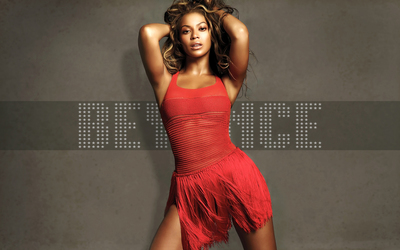 Beyonce in a red dress and with both hands in her hair wallpaper