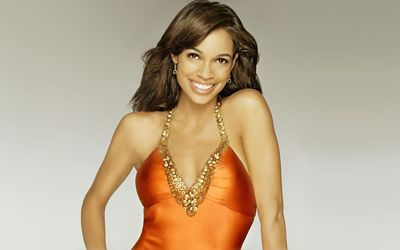 Rosario Dawson with an orange dress wallpaper
