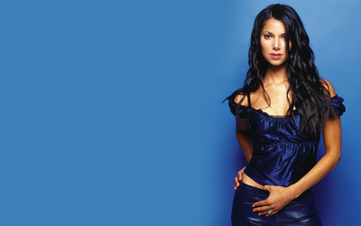 Roselyn Sanchez against a blue wall wallpaper