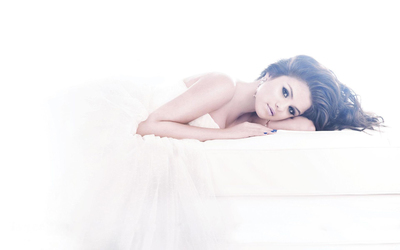 Selena Gomez lying on the white bed wallpaper