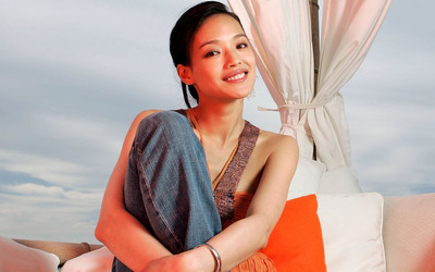 Shu Qi smiling with hands crossed on her leg wallpaper
