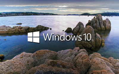 Windows 10 white text logo on the rocky lake shore wallpaper