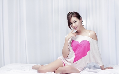 Beautiful asian redhead lying on the bed wallpaper