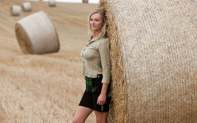 Blonde leaning on a hay bale wallpaper