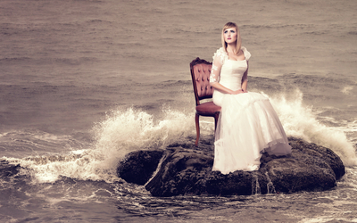 Bride sitting on a chair in the sea wallpaper