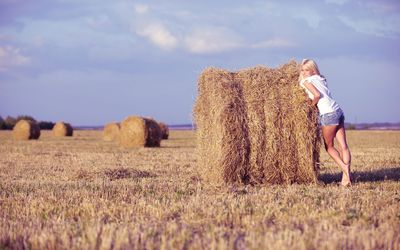 Cute blonde girl leaning on a hay bale wallpaper