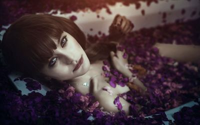 Girl bathing in a tub full of petals wallpaper