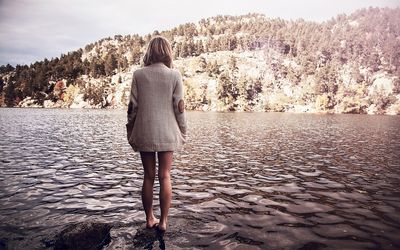 Girl standing on the rock in the river wallpaper