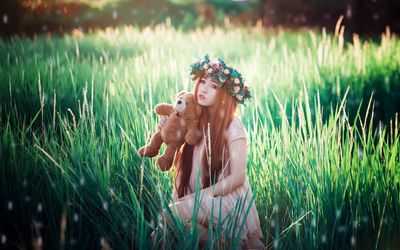 Girl with a teddy bear in the grass wallpaper