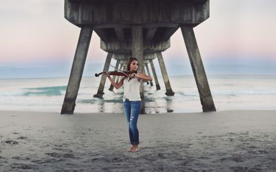 Girl with a violin on the beach Wallpaper