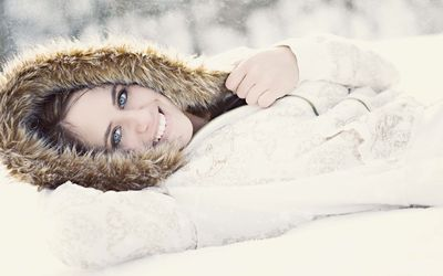 Girl with blue eyes lying in the snow wallpaper