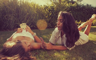 Girls playing cards in the grass wallpaper
