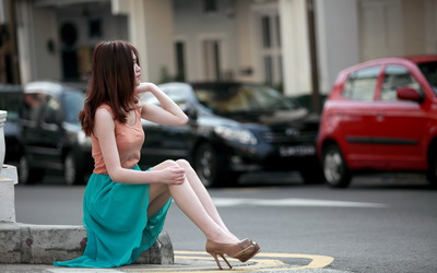 Model sitting on the sidewalk wallpaper