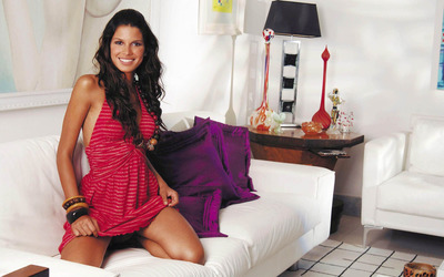 Raica Oliveira with a red dress on a sofa wallpaper
