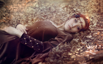 Redhead lying on autumn leaves wallpaper