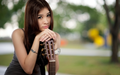 Sad asian girl with a guitar wallpaper