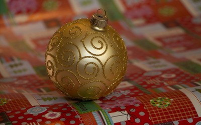 Golden bauble on Christmas wrapping paper wallpaper