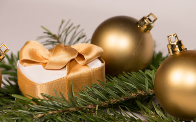 Golden baubles and present on a fir branch wallpaper