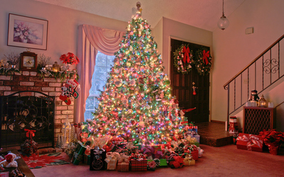 Many gifts under the glowing Christmas tree wallpaper