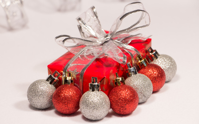 Red and silver baubles by the Christmas present wallpaper