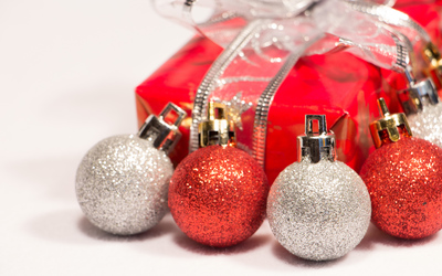 Red and silver baubles with a Christmas present wallpaper
