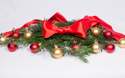 Red ribbon and baubles on fir branches wallpaper