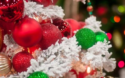 Sparkly red and green baubles on the snowy Christmas tree wallpaper