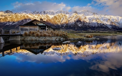 Amazing mountain view behind the hut by the lake Wallpaper