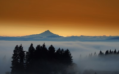 Amazing sunset behind the mountain rising from the fog wallpaper