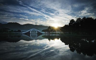 Bridge in the park across the calm water wallpaper