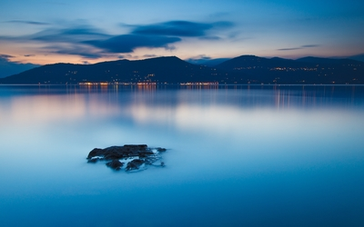 Calm lake at sunset by the city lights wallpaper