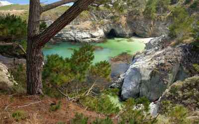 Caves in the rocky small bay shore wallpaper