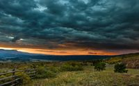 Dark heavy clouds pressing the sunset behind the mountains wallpaper 2560x1600 jpg