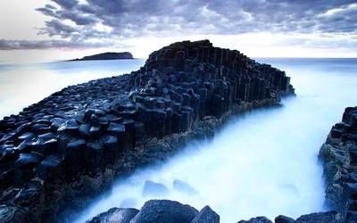 Dark rocky pillars in the ocean Wallpaper