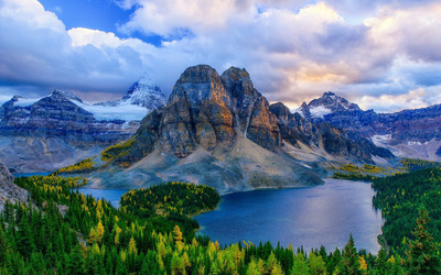 Fluffy clouds above the rocky mountains Wallpaper