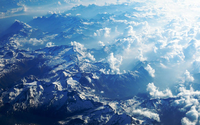 Fluffy clouds above the snowy mountains wallpaper