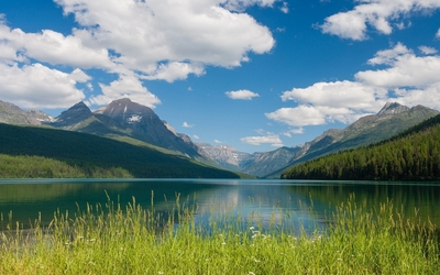 Fluffy white clouds in the blue sky above the mountain lake wallpaper