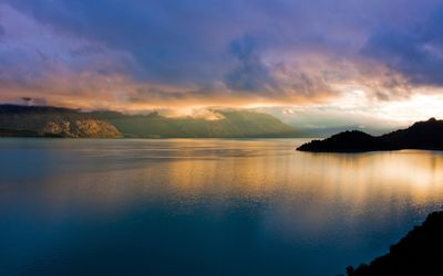 Foggy mountains by the calm water at sunset Wallpaper