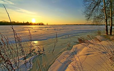 Golden sunset above frozen water wallpaper